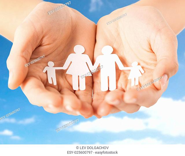 people concept - close up of female hands holding paper family pictogram over blue sky and clouds background