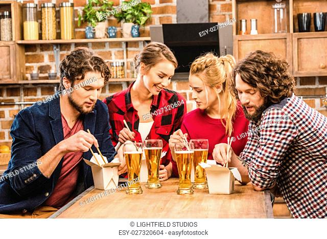 Happy friends eating noodles and drinking beer at home party