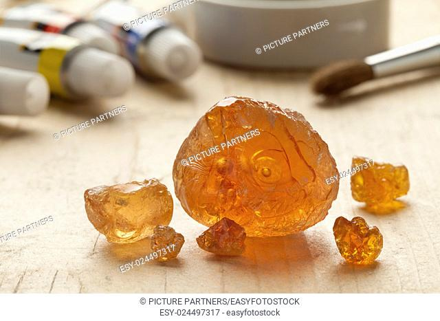 Pieces of Gum arabic with paint and paintbrushes in the background