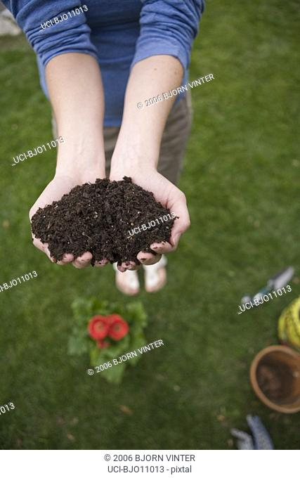 Woman holding handfuls of dirt