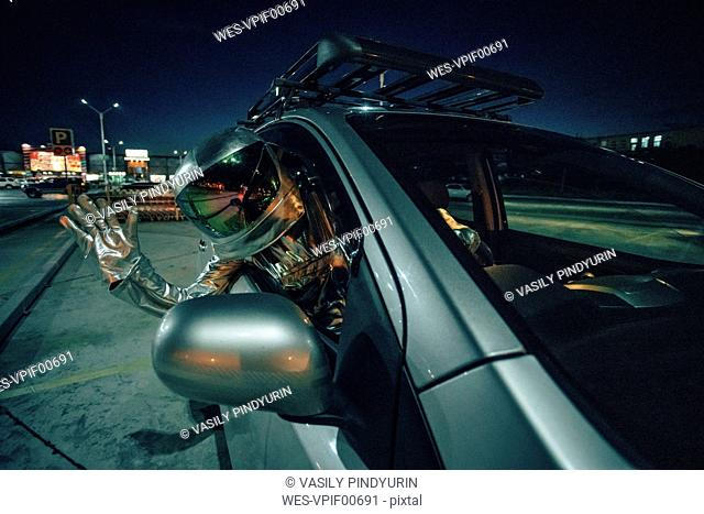 Spaceman waving out of car at night