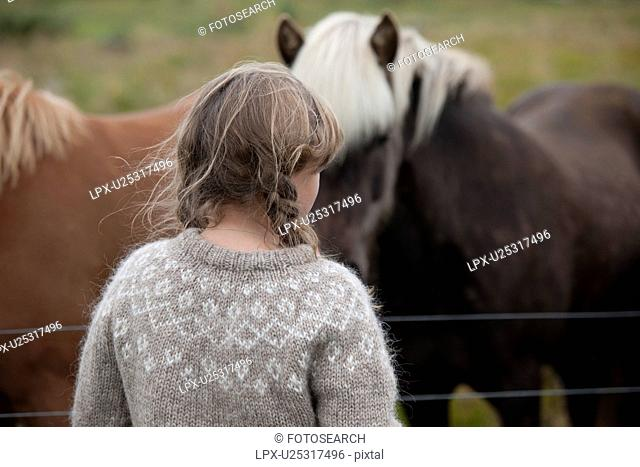 Head and back of girl with messy hair in knit sweater in front of Icelandic horses