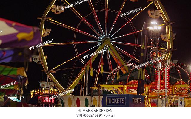 Slow motion wide shot of Ferris Wheel at amusement park at night / Salt Lake City, Utah, United States