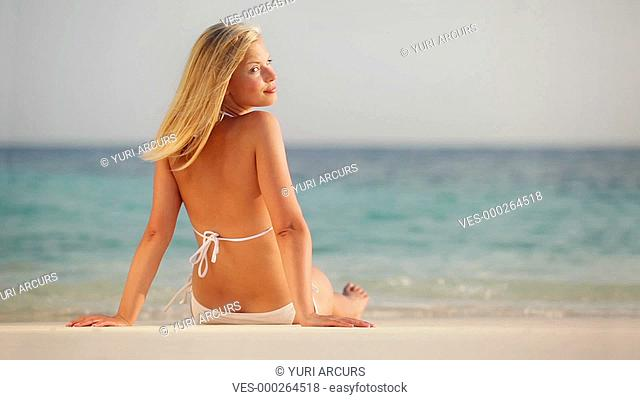 Footage of an attractive young woman relaxing on the beach looking at you over her shoulder