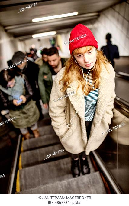 Girl, teenager, with red beanie and headphones in ear on escalator of a subway station, Cologne, North Rhine-Westphalia, Germany