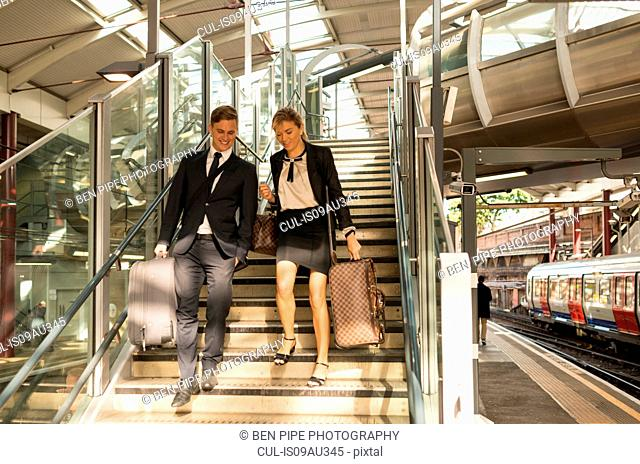Businessman and businesswoman coming down stairs, Underground station, London, UK