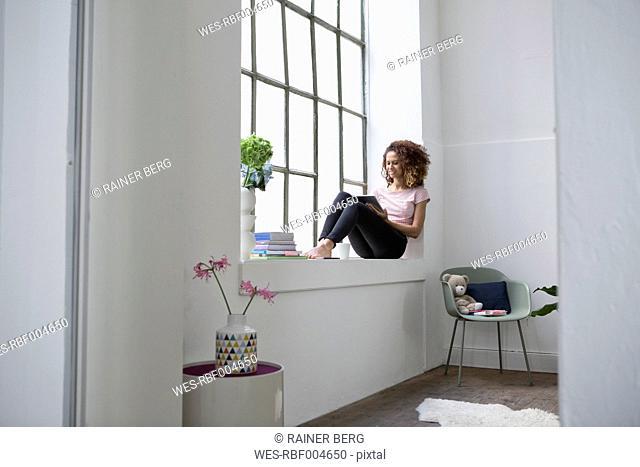 Woman sitting on window sill using digital tablet