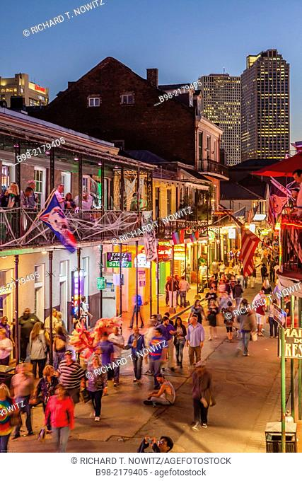 Tourists crowd Bourbon Street in New Orleans' French Quarter at twilight, looking for nightlife