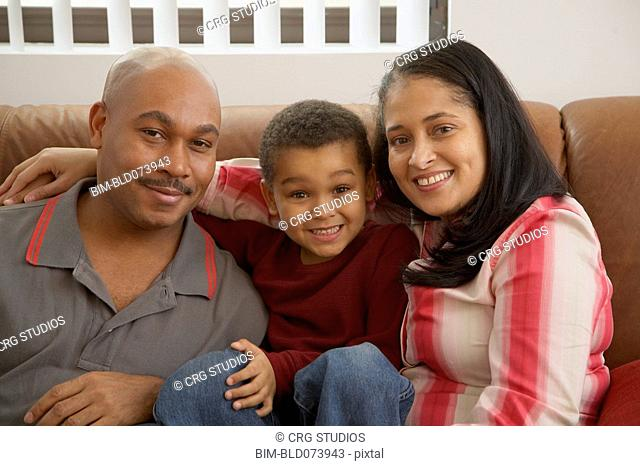 Mixed race boy snuggling on couch with parents
