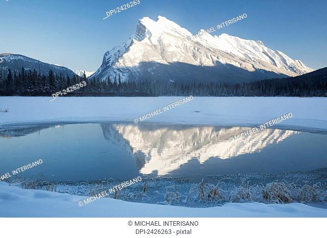 Snow covered mountain reflecting in open water on a snow covered lake and blue sky; Banff, Alberta, Canada