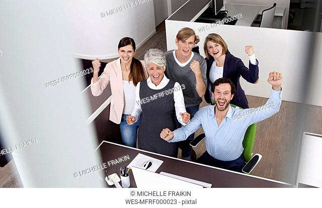 Happy business team celebrating at desk in office