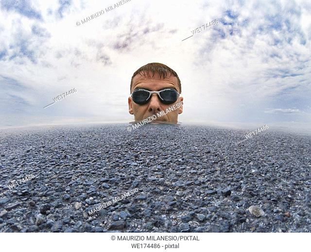 Serious man with swimming goggles, nestled in the middle of an ocean of asphalt, sea water and cloudy sky