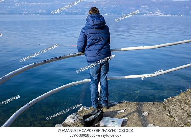 teenager on the shore of Lake Maggiore are fishing in the winter on a sunny day
