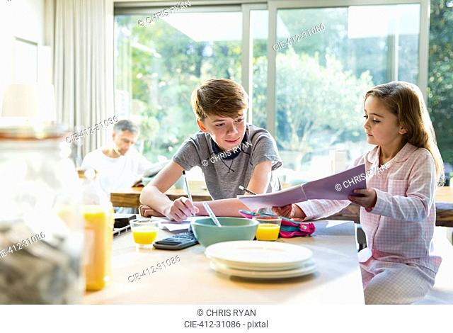 Brother and sister eating breakfast and doing homework