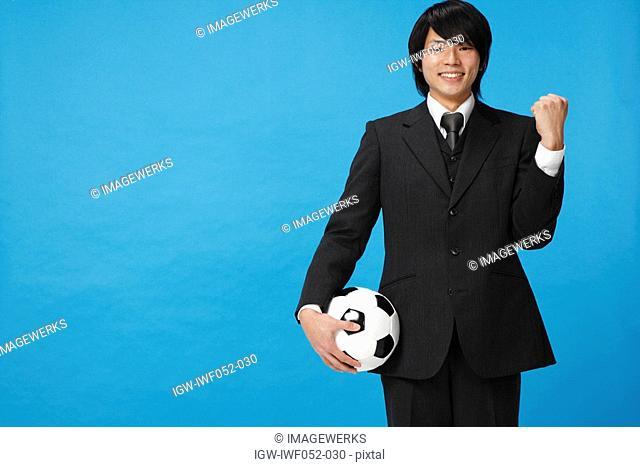 Businessman holding soccer ball, smiling, portrait