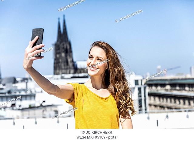 Germany, Cologne, portrait of smiling woman taking selfie with smartphone on roof terrace