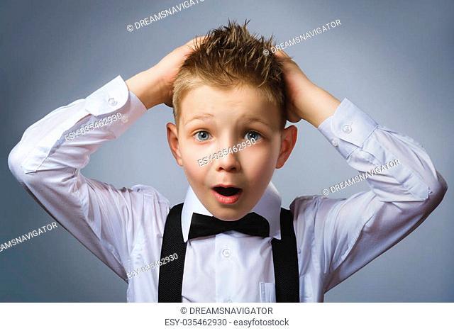 Closeup portrait headshot nervous anxious stressed afraid boy isolated grey background. Negative emotion facial expression