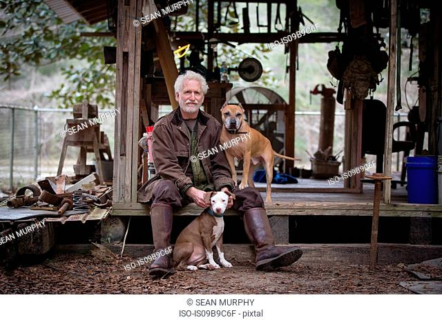 Man with pet dogs by wooden work hut