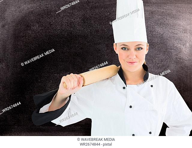 Female chef holding rolling pin against black background