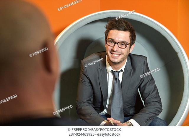 Image of young businessman interviewing man at office