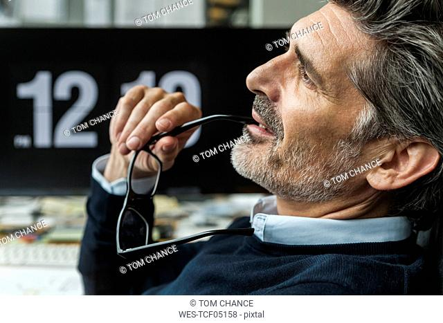 Mature man holding glasses, thinking about solutions