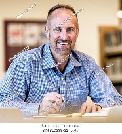 Smiling Caucasian businessman writing on notepad