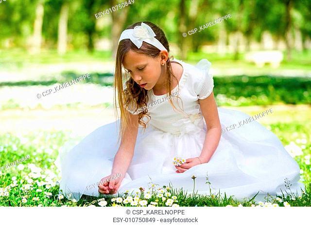 Sweet girl in white dress picking flowers