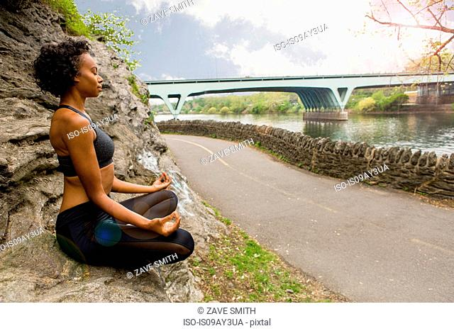 Woman sitting cross legged on rock meditating