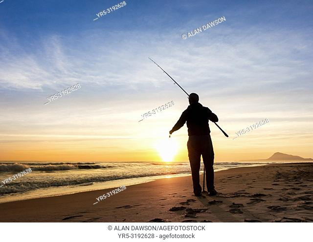 Man fishing from beach near Oliva at sunrise on the Costa del Azahar near Denia, Valencia province, Spain, Europe