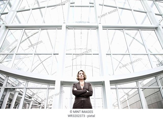 A portrait looking up at a Caucasian businesswoman standing next to a large graphic pattern on a window in a convention centre