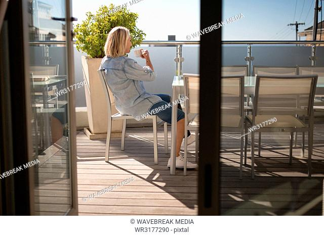 Disabled woman having coffee in the balcony