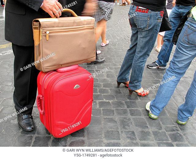 businessman with luggage standing in street in city town