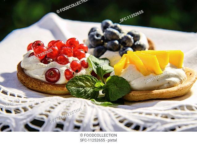 Three fruit tarts with cream, redcurrants, blueberries and mango