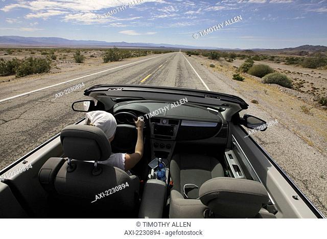 USA, Young woman driving her convertible car through desert along Route 66; California