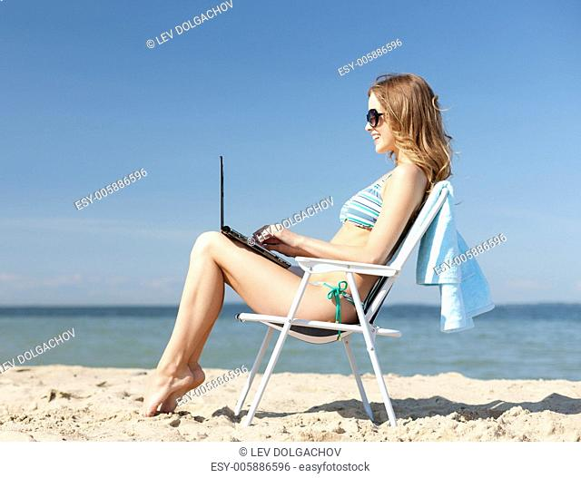 summer holidays, vacation, technology and internet - girl looking at tablet pc on the beach chair