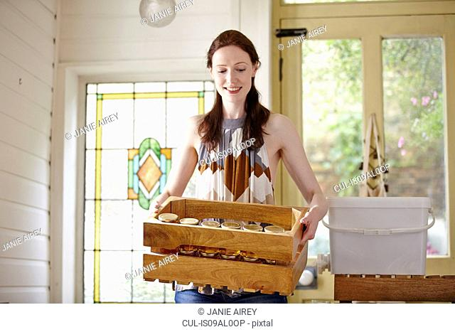 Female beekeeper in kitchen carrying a crate of honey jars from beehive