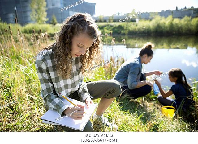 Schoolgirl taking notes on field trip at pond