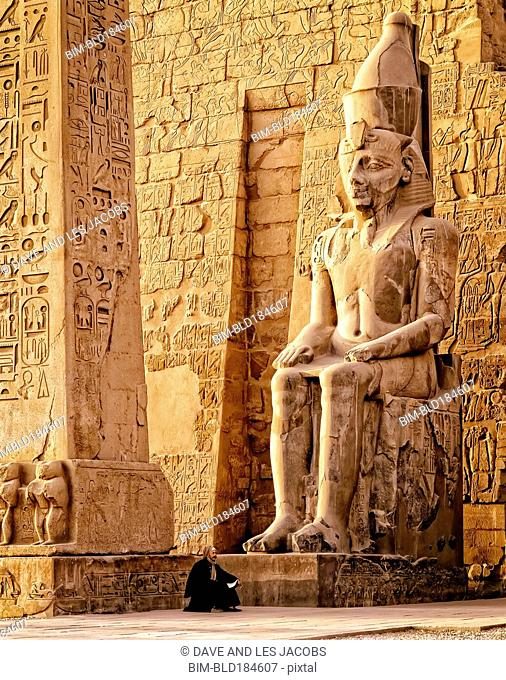 Middle Eastern man under ancient statue, Luxor, Egypt