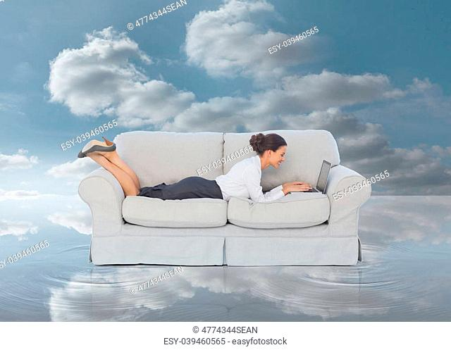 Businesswoman lying on couch and typing on her laptop in front of the blue sky