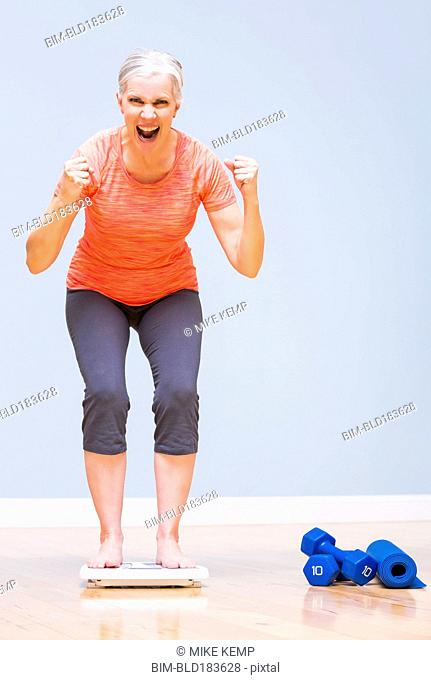 Caucasian woman cheering on scale