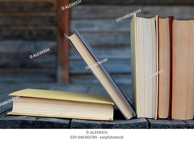 books standing different objects on a wooden table on a background of blurred summer foliage