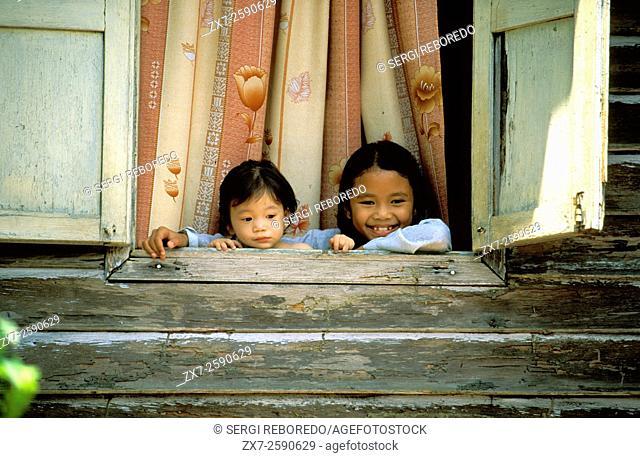 Children in a windows. Wood house. Kota Bharu, Kelantan. Malaysia