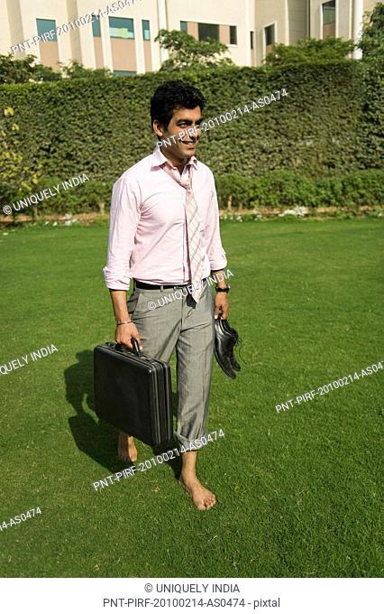 Businessman walking barefoot in a park, Gurgaon, Haryana, India