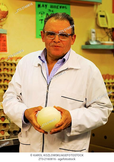 Unidentified salesman holding an egg in Mercat de Santa Caterina - Fresh Food Market in Barcelona, Catalonia, Spain