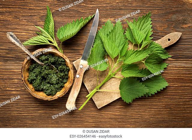 Nettle fresh green leaves on a wooden background