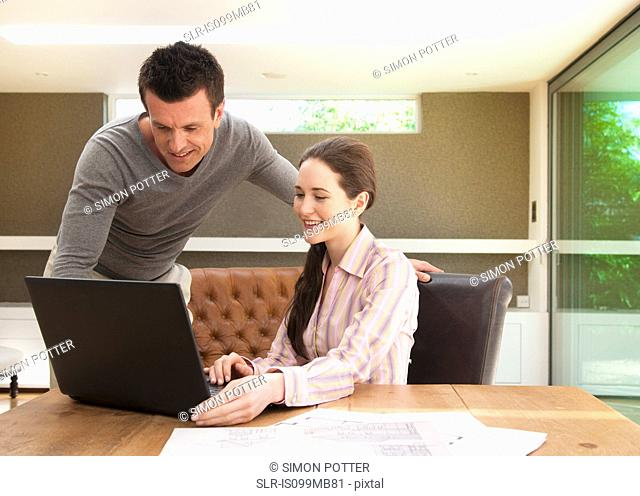 Couple using laptop in home office