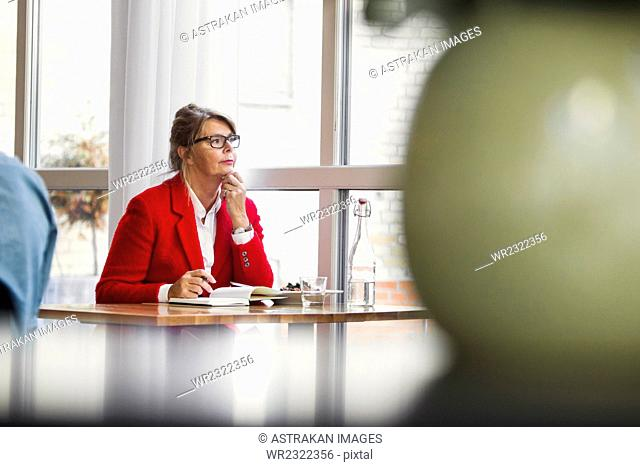 Thought businesswoman sitting at table in restaurant