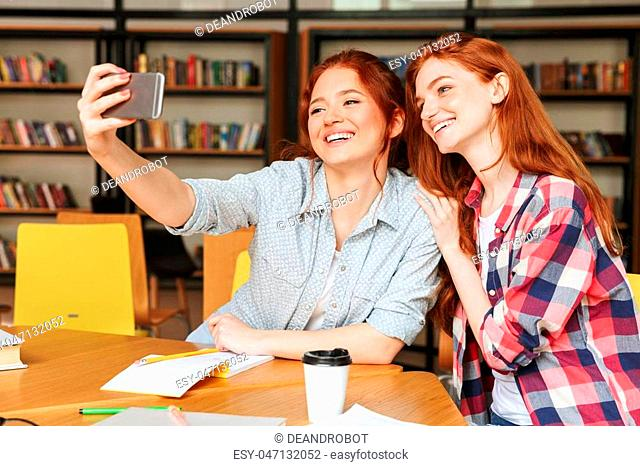 Portrait of a two happy teenage girls taking selfie with mobile phone while sitting at the library