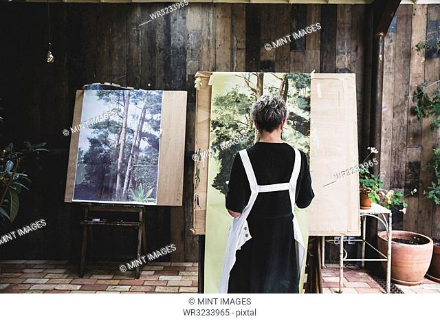 Senior woman wearing black dress and white apron standing in studio, working on painting of trees in forest
