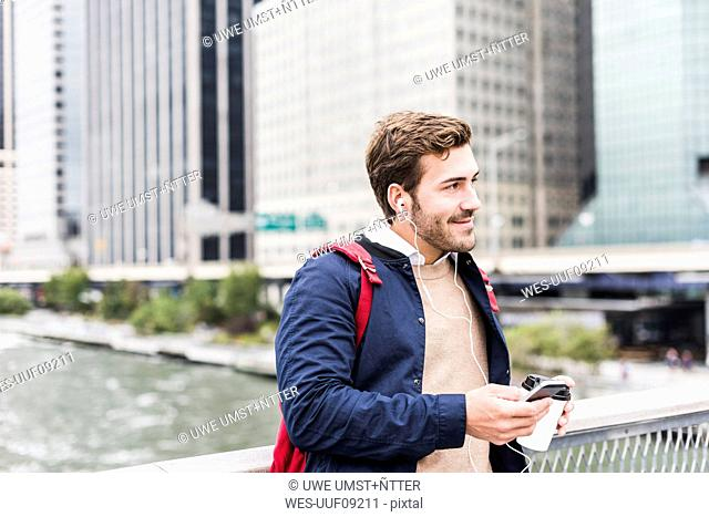 USA, New York, Businessan in Manhattan using smart phone and earphones